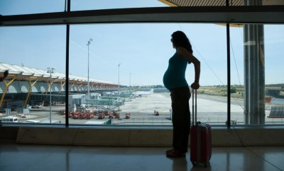 woman pregnant silhouette waiting to fly in airport hall