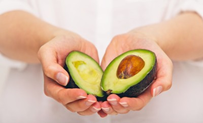 Female hand holding sliced avocado