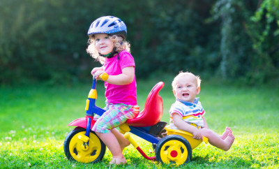 Two happy kids, adorable curly toddler girl and a funny cute baby boy, brother and sister, playing together riding a bike, first colorful tricycle, having fun in the garden on a sunny summer day