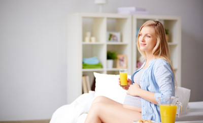 Dreamy pregnant woman drinking orange juice and stroking her belly