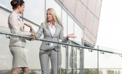 Young businesswoman arguing with female colleague at office balcony