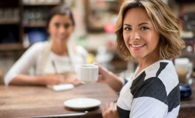 Happy woman drinking a cup of coffee at a cafe