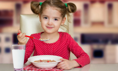 Little girl have a meal home. Kid healthy food. Smiling child eats snack with milk.
