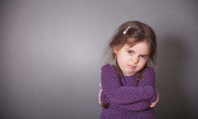 A little cute Girl is sulking. She is wearing a purple shirt in front of a gray background.