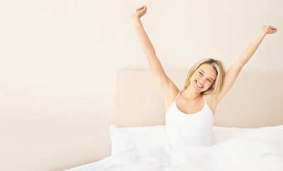 Portrait of a beautiful young woman stretching on bed with copy space