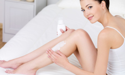 Young beautiful woman applying body lotion on her attractive legs - indoors