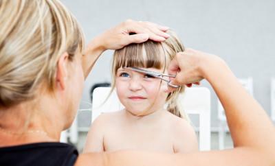 Woman cutting young girls hair