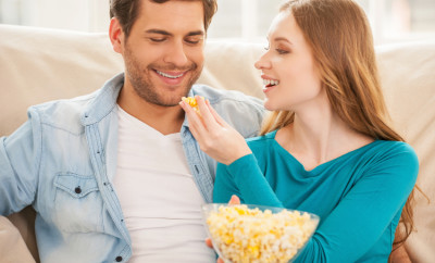 Couple eating popcorn. Beautiful young couple sitting on the couch together and watching TV