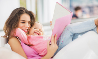 Happy young mother having fun with her little daughter while reading a book.
