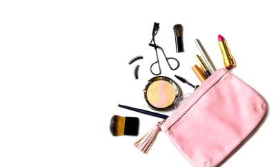 make up bag with cosmetics and brushes isolated on white background