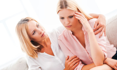 Everything will be ok! Beautiful mature woman consoling her depressed daughter while sitting on sofa