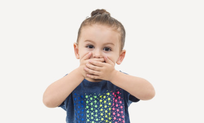 Toddler girl covering mouth with hands against white background, Studio shot. High resolution image taken with Hasselblad H5D 50c and developed from raw