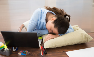 Young Businesswoman Sleeping At Desk In Office
