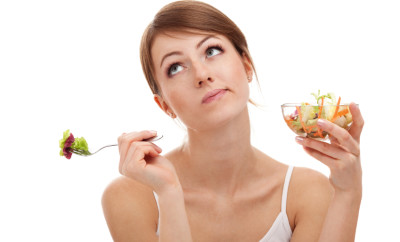 Sad woman on diet with vegetables. Isolated on white background.