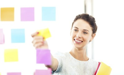 Smiling young businesswoman sticking adhesive notes on glass wall in office. Horizontal shot.