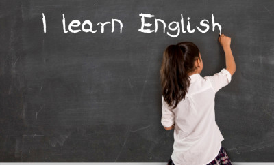 sweet little girl at school with ponytail and uniform writing with chalk on classroom blackboard in English learning concept isolated on white background
