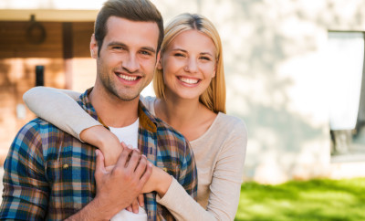 Young and in love. Beautiful young couple bonding to each other and smiling while standing against their new house