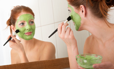 Young woman applying green facial mask in the bathroom