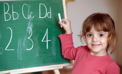 3  years old girl showing hers work on blackboard and holding chalk in her hand
