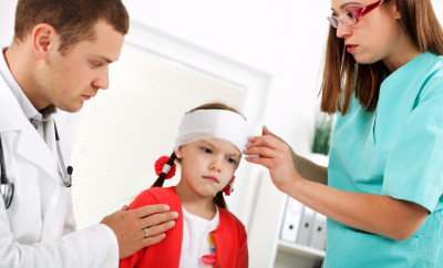 Doctor  and nurse are putting bondage on little girl's head.