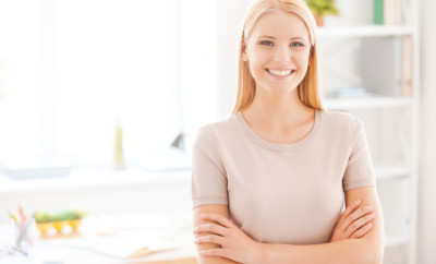 Positive office worker. Beautiful young woman keeping arms crossed and smiling while standing near her working place in office