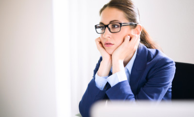 An attractive, smartly dressed young woman with long brown hair and glasses rests her chin on her hands, staring sadly at the computer screen in front of her. Her hair is tied back and she is wearing a blue shirt and jacket. Camera: 36MP Nikon D800E.