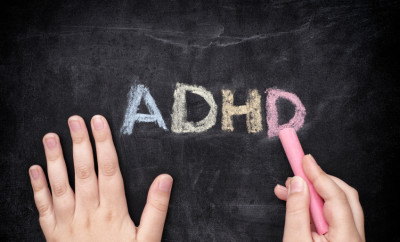 Child writing ADHD on blackboard. ADHD is Attention deficit hyperactivity disorder.