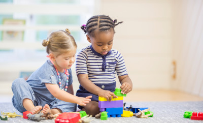 A multi-ethnic group of toddlers are sitting on the floor playing with toy building blocks.