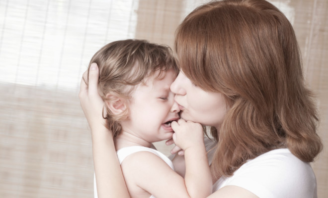 Side view of young mother comforts crying baby girl