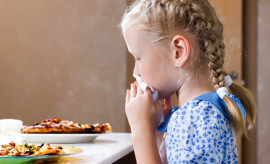Pretty little girl sitting at the dinner table eating homemade pizza wiping her mouth with a napkin while turning to glance at the camera with a serious expression