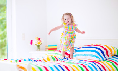 Cute little curly toddler girl in a colorful dress jumping on a big white bed laughing and having fun on a sunny weekend morning in a bedroom