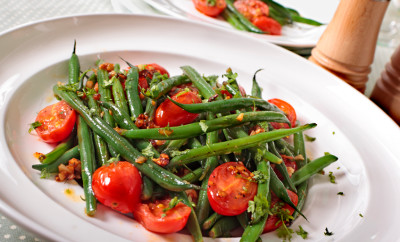 Green beans and tomato salad on white plate.  Alternative image in this collection: