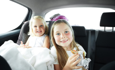 Portrait of a little girl eating in the car with her sister sitting next to her