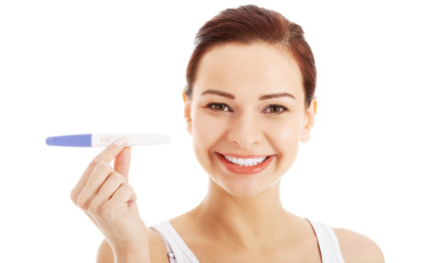 Happy beautiful young woman with pregnancy test. Isolated on white.