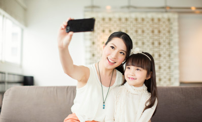A young Chinese mother takes a selfie of herself and her daughter.