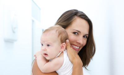 Close up portrait of a mother smiling with baby at home