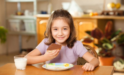 little girl having breakfast: eating chocolate cream on a slice of bread