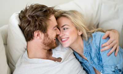 Loving couple relaxing at home lying on the sofa - relationship concepts