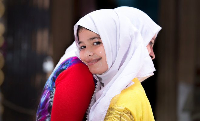 Cheerful and happy Muslim women with traditional veil embracing each other on the occasion of Eid.