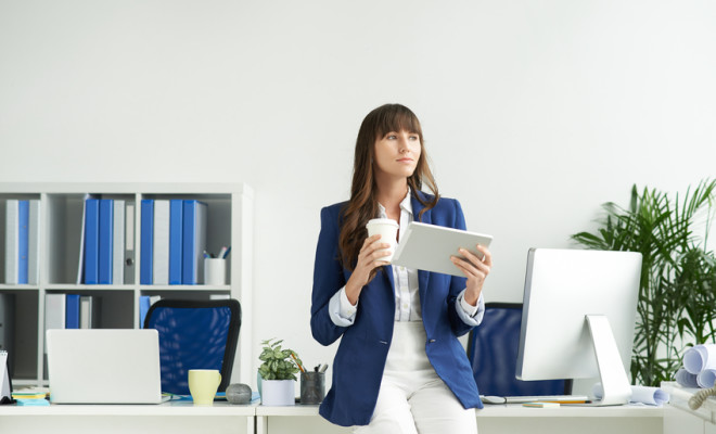 Pensive business woman with digital tablet drinking coffee