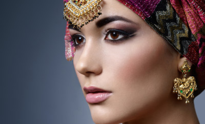 Beautiful fashion east  woman portrait with oriental accessories. Indian arabic girl with  colored turban and beauty jewels. Hindu model with perfect make-up. India. Asia