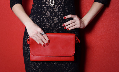 Fashionable woman with a red bag in her hands and black evening dress