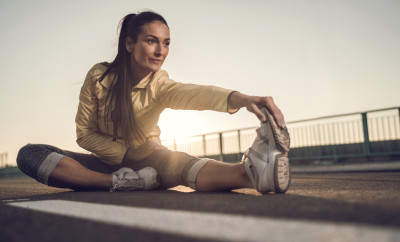Young smiling woman doing relaxation exercise while sitting on a road at sunset and stretching her leg.