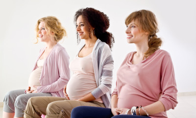 Three preety, pregnant young adult women sitting on gym balls, looking in one direction and smiling.