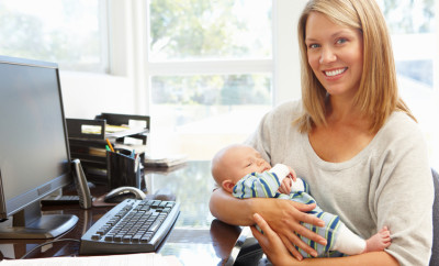 Mother working in home office with baby smiling at the camera