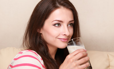 Happy woman drinking milk from glass sitting on sofa