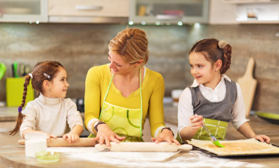 Little girls assisting their mother in baking.