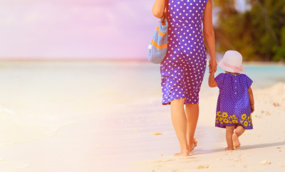 rear view of mother and little daughter walking on tropical beach