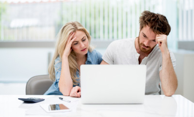 Young couple in financial trouble looking very worried - home finances concepts