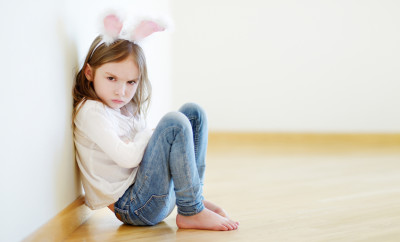 Very angry little girl wearing bunny ears sitting on a floor at home